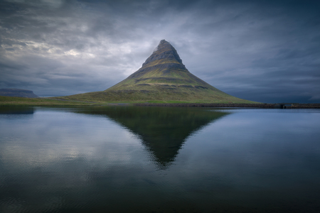 Iceland landscape photo of mountain near lake at beautiful dusk with reflection in calm afternoon. Stock fotó