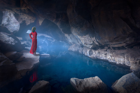 Iceland landscape fine art photo of lady in red dress proudly standing in spooky and misty cave with hot blue water.
