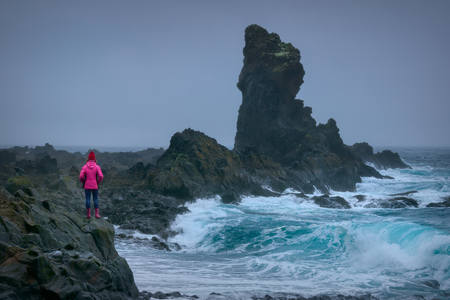 Iceland landscape photo of adventurous and brave girl who proudly standing in front of huge rock near dangerous waves at overcast day.