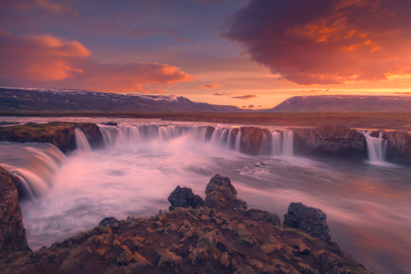 Iceland landscape photo of huge waterfall at beautiful and idyllic sunset.