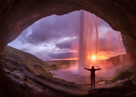 Iceland landscape photo of adventurous girl with his arms raised who proudly standing behind the huge watrfall at idyllic sunset. Stock fotó