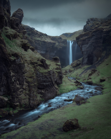 Iceland landscape photo of Kvernufoss waterfall and canyon at mystical cloudy and moody day.