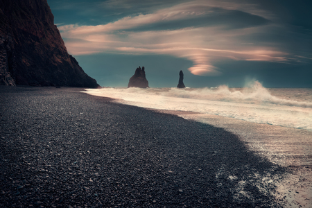Iceland landscape photo of volcanic beach and rock spires with powerful waves under lenticular clouds at stormy morning. Stock fotó