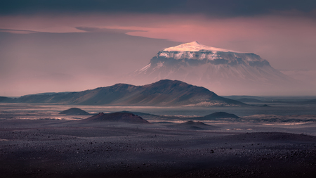 Iceland landscape photo in deserted rocky highlands with famous Icelandic mountain covered with snow at beautiful sunrise.