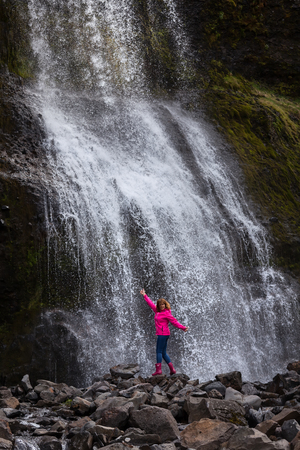 Iceland landscape photo of brave girl who proudly standing with his arms raised in front of waterfall at overcast day.