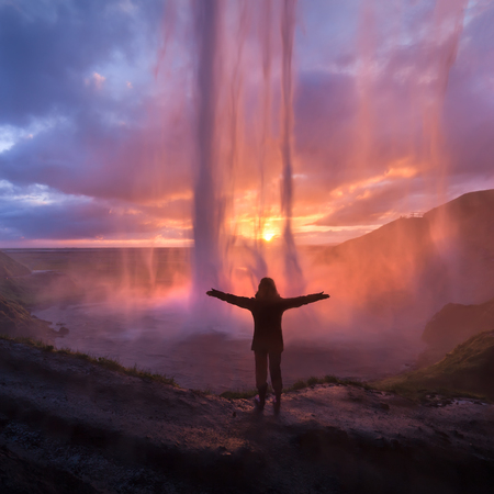 Iceland landscape photo of girl who proudly standing with his arms raised in front of waterfall at idyllic sunset. God and spirituality concept.