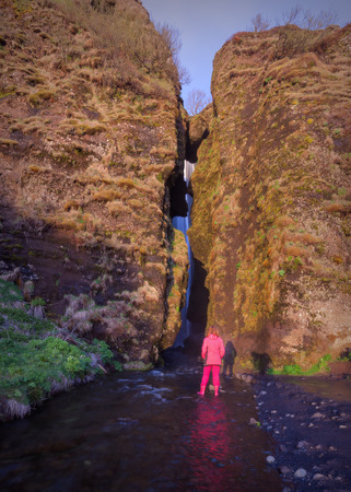 Girl standing in front of entrance to the narrow canyon on the way to the hidden Gljufrabui waterfall at sunset. Stock fotó