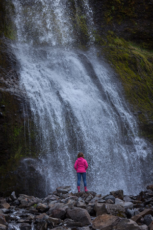 Iceland landscape photo of girl who standing and contemplating in front of waterfall at beautiful morning. Stock fotó