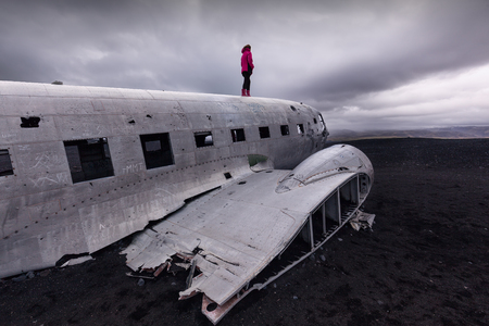 Iceland landscape photo of girl standing on top of the famous crashed airplane wreckage at cloudy weather.
