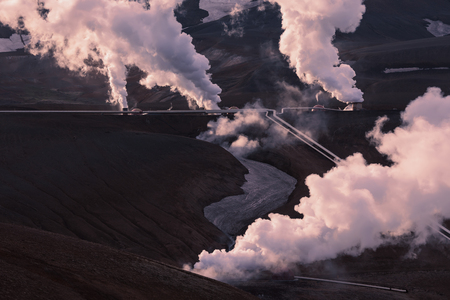 Pipelines with steam fumes at Krafla geothermal power station as green energy on sunny day. Stock fotó