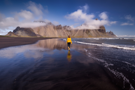 Iceland landscape photo of girl walking at black sand volcanic beach towards the mountains at idyllic sunny day.