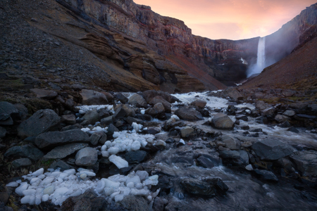 Iceland landscape photo of high powerful waterfall with pieces of ice in foreground at sunset.
