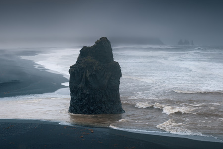 Iceland landscape photo of black sand beach at overcast weather with huge rock at stormy morning.