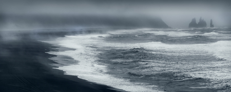 Iceland landscape photo panorama of volcanic beach at overcast weather with powerful waves at stormy morning. Stock fotó