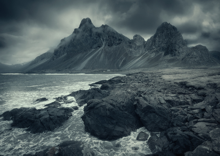 Iceland landscape photo of moody mountain peaks and dramatic waves with coastline in foreground at overcat day.
