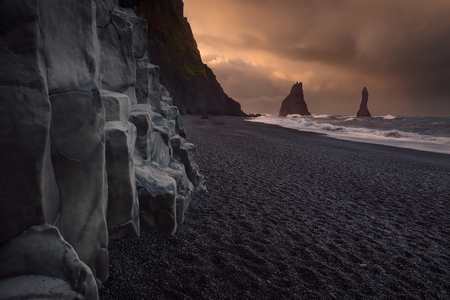 Iceland landscape photo of mystical black volcanic beach at cloudy sunrise with powerful waves and basalt columns. Stock fotó