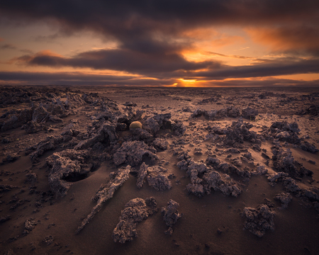 Iceland landscape photo of dramatic lava desert at moody sunset with unusual rock formation.