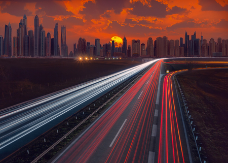 Compositing image as futuristic concept of cityscape with many skyscrapers in Dubai at idyllic sunrise with light trails on motorway. Transportation concept.
