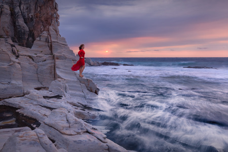 Conceptual artistic photo of woman who standing in front of sea on wild rocky beach at windy sunrise. Freedom concept.