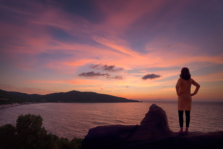Photo of girl who standing on edge of the cliff in front of seascape at beautiful dawn. Lifestyle and travel concept.