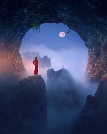 Artistic photo of lone girl standing on edge of the cliff and contemplating beautiful mountains peaks at moonlight. Fantasy concept.