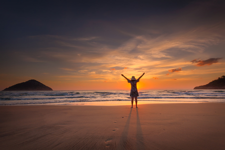 Happy woman with his arms raised next to the sandy paradise beach at sunrise. Success and freedom concept. Stock fotó