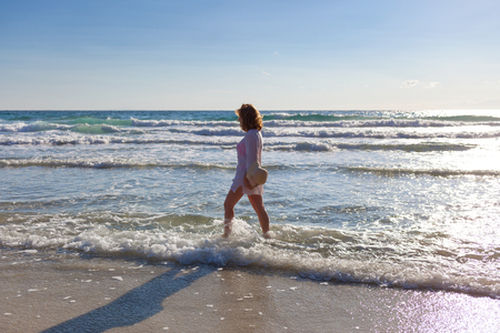 Carefree girl walking through the waves on the sandy paradise beach at sunrise. Lifestyle and freedom concept. Stock fotó