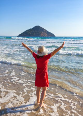 Cheerful girl with his arms raised next to the sandy paradise beach at sunrise. Lifestyle and freedom concept.