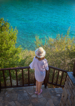 Photo of girl who standing and contemplating in front of sea shore at beautiful morning. Lifestyle and travel concept. Stock fotó