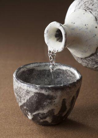 Water in een klei glas wordt gegoten Stockfoto