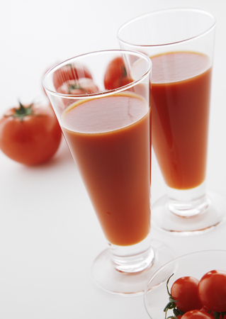 Fresh tomatoes and two glasses full of tomato juice. Stockfoto