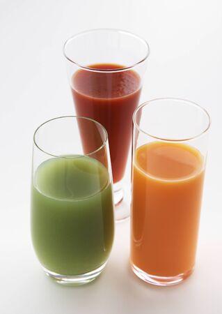 Drie Glazen van vruchtensappen op White Garden Tafel.