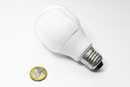 A neon bulb and a 1 euro coin to indicate the savings that you have using this type of lighting photo