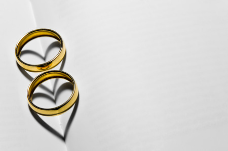 Two wedding rings on top of the blank pages that form two hearts with their shadows Stockfoto
