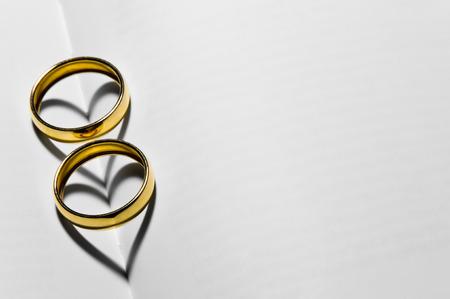 Zwei Hochzeitsringe auf der Oberseite der leeren Seiten, die zwei Herzen mit ihren Schatten bilden Standard-Bild - 39656265