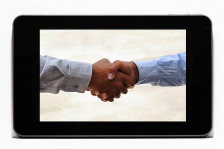 Closeup of a handshake on a tablet as a business concept