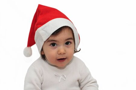 Closeup of a curious little girl with Christmas hat photo