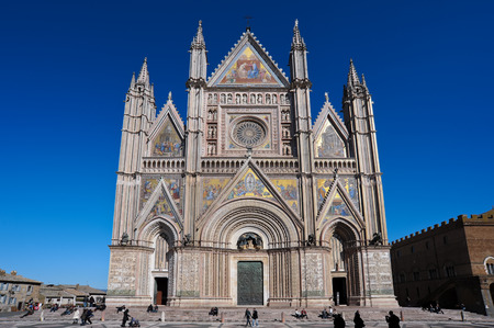 Facade of the Cathedral of Orvieto in Italy with tourists