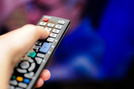 television show: Closeup of a hand holding a remote control for the television Stock Photo