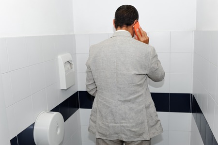 Businessman working in the bathroom with his smartphone as a concept to work anywhere Stock Photo