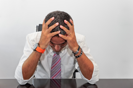 Portrait of a businessman with his hands to his head as a concept of failure in business