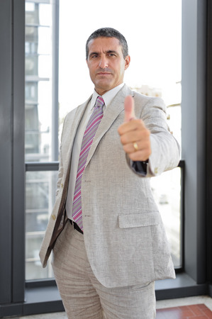 hands lifted up: Businessman with thumbs up in outdoor as business concept