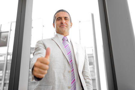 hands lifted up: Perspective of a smiling businessman with thumb raised as a concept of success in business