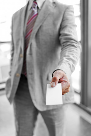 Businessman that delivers a business card as a business concept photo