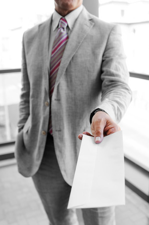 missive: Businessman handing a mailing envelope as a business concept