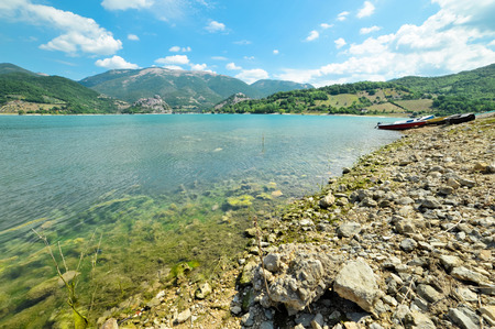 tora: Wide shot of the rocky beach of Lake Turano in Italy