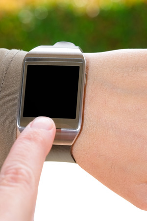 partially: Close up of a partially isolated smartwatch and an index finger as a concept of wearable technology