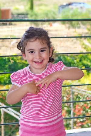 bashfulness: Portrait of a smiling little girl as a concept of happiness Stock Photo