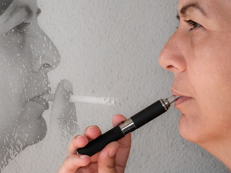 Close up of a smoker who has replaced the cigarette with electronic cigarette photo
