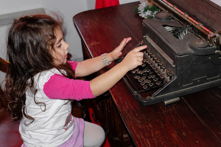 Little girl beats on the typewriter as a concept of childhood game photo